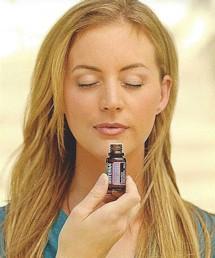 Gitl smelling essemtial oil from bottle