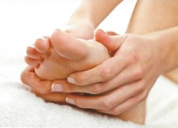Massaging essential oils into foot